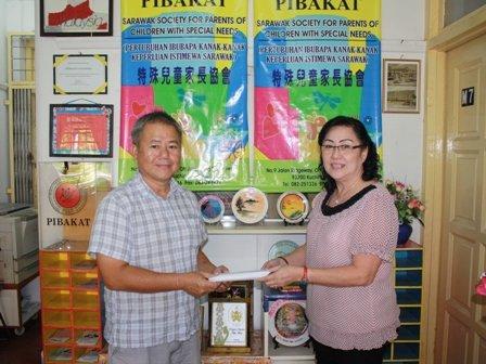 Bro. Lau (左)赠送义卖券给特殊儿童家长协会执行秘书多丽丝郭(Doris Kuek)。