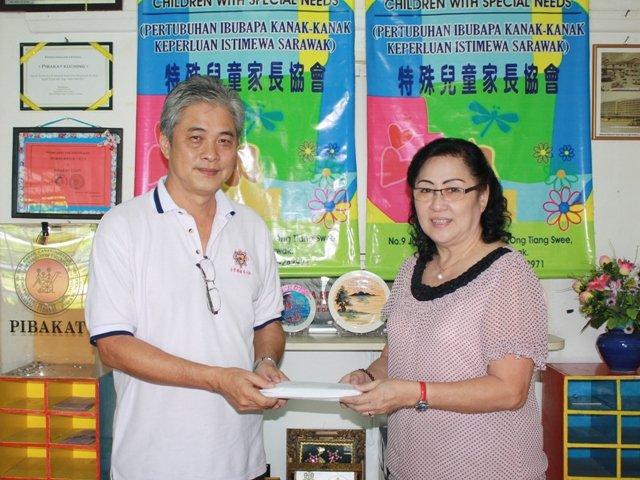 古晋居士林密宗团团长黄亚瑞(左)赠送义卖券给特殊儿童家长协会执行秘书多丽丝郭(Doris Kuek)。