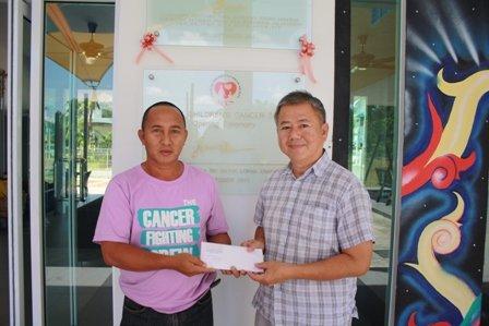 Bro. Lau(右)赠送义卖券给癌症儿童协会(SCCS)代表。