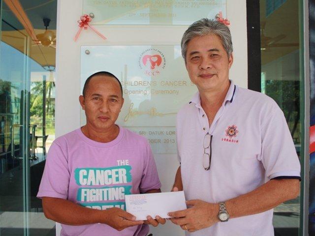 古晋居士林密宗团团长黄亚瑞(右)赠送义卖券给癌症儿童协会(SCCS)代表。